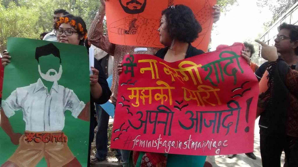 Peaceful protesters standing with posters at Mandir Marg.